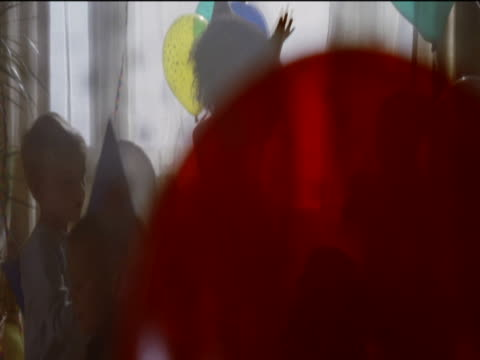 five young children play with multi-coloured balloons in a living room at a birthday party - erkerfenster stock-videos und b-roll-filmmaterial