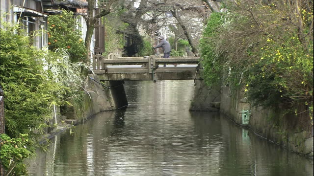 fixed shot of a narrow waterway and a bridge crossing over the canal, an old lady crossing the bridge. - narrow stock videos and b-roll footage