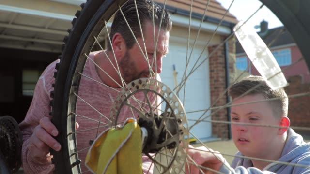 fixing a bike at home - disability stock videos & royalty-free footage