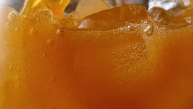vídeos de stock e filmes b-roll de fizzy orange juice drink pouring into glass - juicy