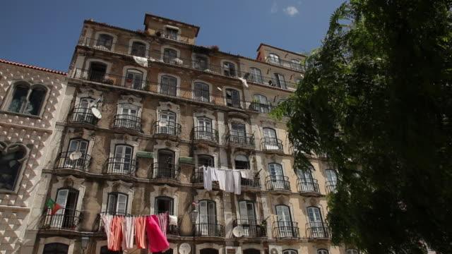 vídeos y material grabado en eventos de stock de ms la flag and laundry hanging at old building / lisbon, portugal - hacer la colada