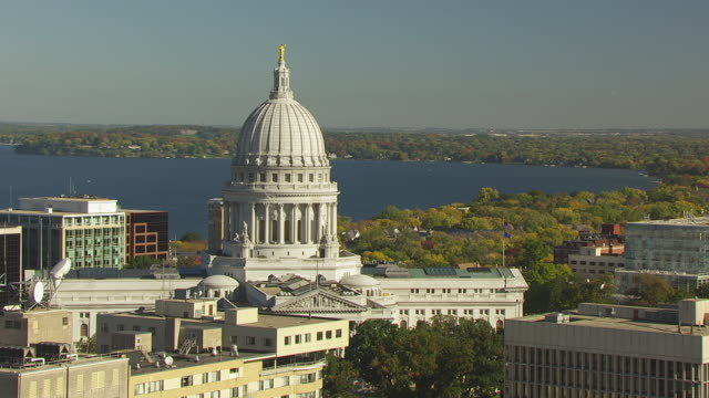 WS ZO AERIAL POV US Flag and Wisconsin State Flag waving on top of Wisconsin state capital building / Madison, Wisconsin, United States