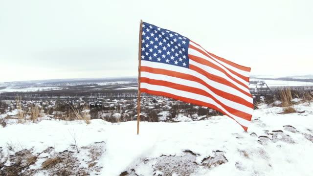 stockvideo's en b-roll-footage met usa vlag in winter gesneeuwde hill - paalzitten