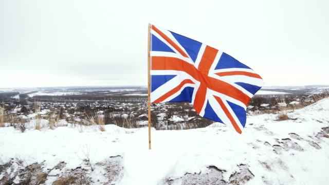 stockvideo's en b-roll-footage met uk vlag in winter gesneeuwde hill - paalzitten