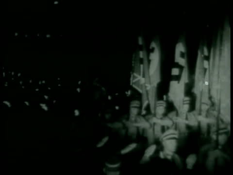 stockvideo's en b-roll-footage met night flag bearers marching w/ torches bg ms german nazi hitler saluting soft focus soldier fg wwii - 1938