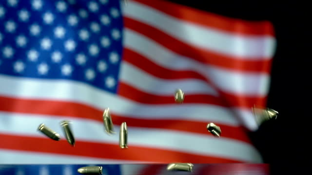 usa flag behind bullets falling in slow motion - arma da fuoco video stock e b–roll