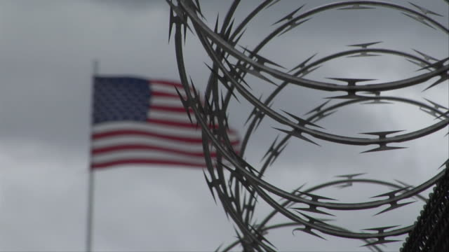 vidéos et rushes de cu flag blowing in wind behind roll of barbed-wire / new york, new york, usa - fil barbelé