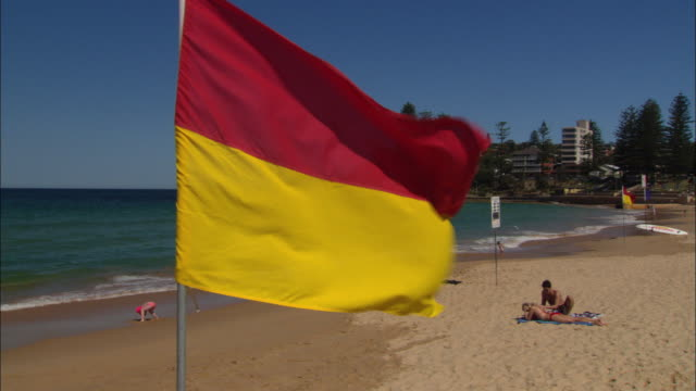 ms tu flag blowing in wind on beach, people relaxing in background, sydney, new south wales, australia - yellow stock videos & royalty-free footage