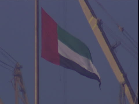 uae flag blows gently in haze in front of large crane dubai - erezione video stock e b–roll