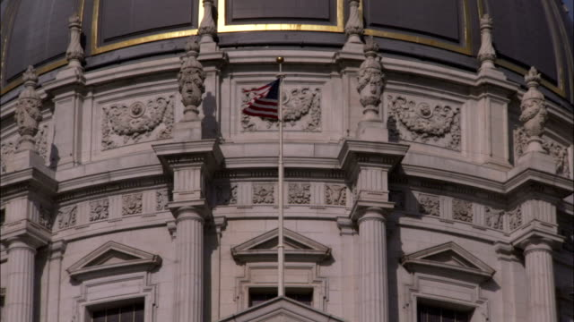 A flag flies above the pediment of the city hall of San Francisco. Available in HD.