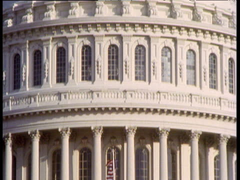 USA flag flies in front of Capitol hill (Congress) building tilt up to top of dome; Washington DC