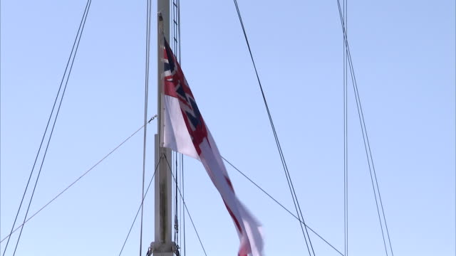 A flag flutters from a ship mast. Available in HD.