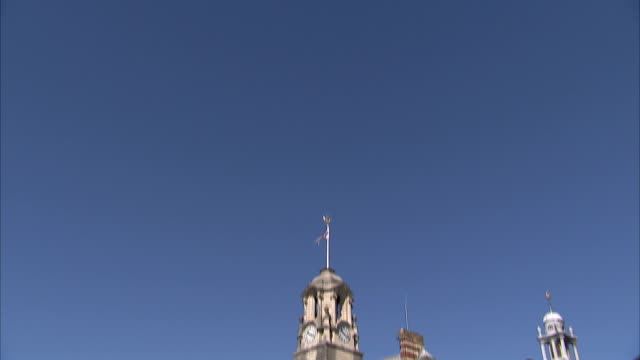 A flag flutters on top of a building on the campus of Britannia Royal Naval College. Available in HD.