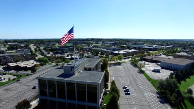 flag flying above election systems & software building. - nebraska stock-videos und b-roll-filmmaterial