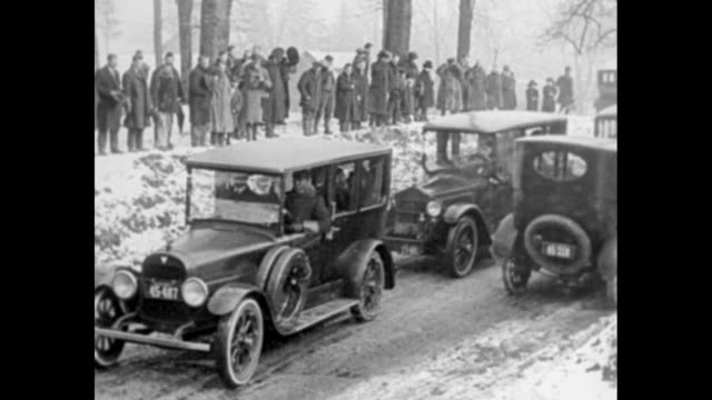 us flag flying at half mast in oyster bay / policemen on horses leading funeral procession of automobiles driving down street snow on ground / hearse... - 1910 1919 stock videos and b-roll footage