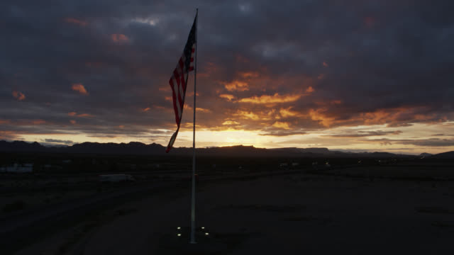 vidéos et rushes de us flag flying beside interstate at sunset - drone shot - sud ouest américain