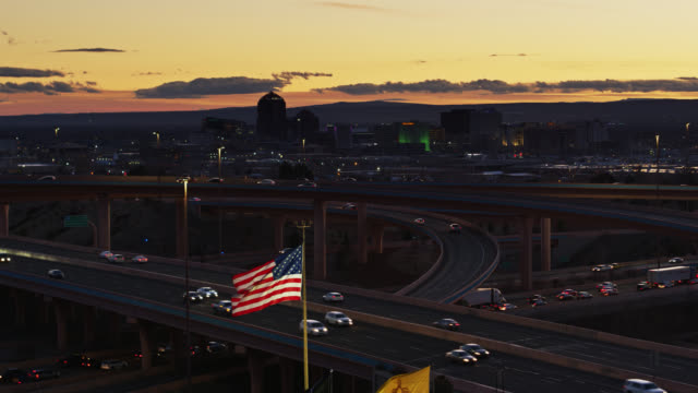vídeos de stock e filmes b-roll de us flag flying in front of freeway interchange and albuquerque skyline - drone shot - patriotismo