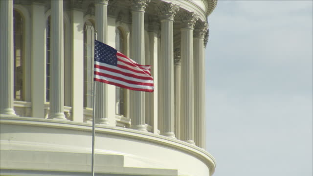 vídeos de stock, filmes e b-roll de us flag flying in front of the capitol building - bandeira