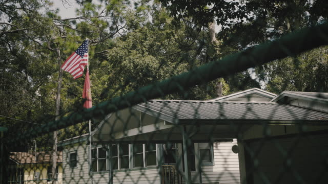 flag in a residential neighborhood behind chain link fence - wire mesh fence stock videos & royalty-free footage