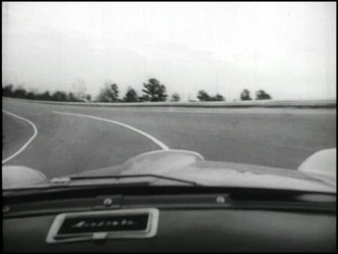 ws flag man on raised platform at raleigh speedway / ws nash metropolitan starts to accelerate on track / ms pov looking through windshield as nash... - 試運転点の映像素材/bロール