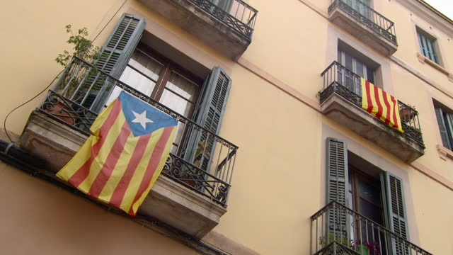flag of catalonia and estelada blava hang from different wrought iron balconies in sunshine on limestone fa�ade - barcelona, spain - hanging stock videos & royalty-free footage