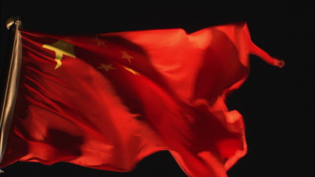 cu flag of china against a dark background - chinese flag stock videos and b-roll footage