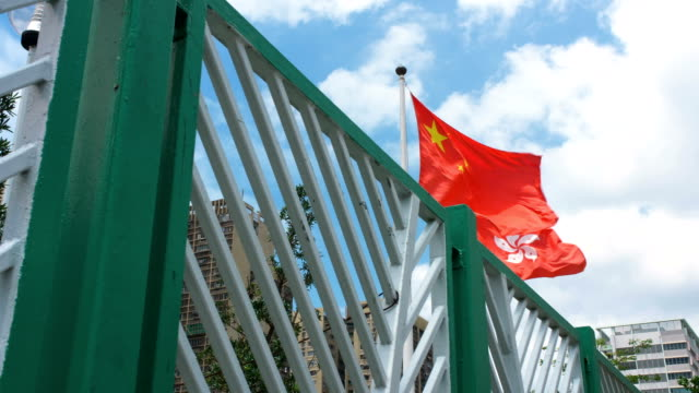 flag of china and hong kong waving at wind with blue sky - chinese flag stock videos & royalty-free footage