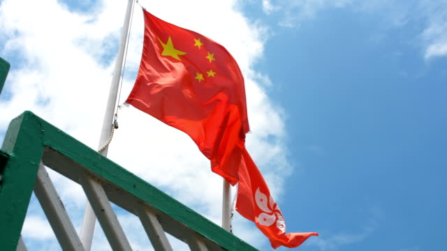 flag of china and hong kong waving at wind with blue sky - hong kong flag stock videos & royalty-free footage