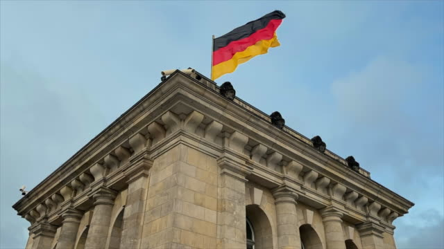 flag of germany blows proudly in the wind, on the reichstag in berlin. - 1933 stock videos & royalty-free footage