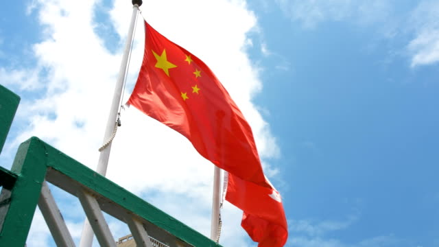 flag of hong kong and china waving at wind with blue sky - chinese flag stock videos & royalty-free footage