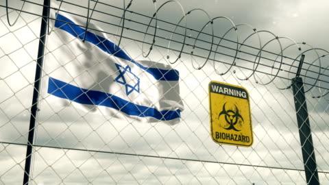 stockvideo's en b-roll-footage met vlag van israël met het teken van biohazard dat van quarantaine waarschuwt. loopbaar. - israël