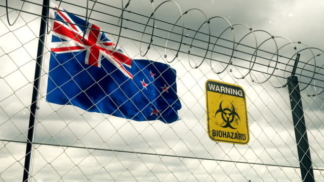 flag of new zealand with biohazard sign warning of quarantine. loopable. - biohazard symbol stock videos & royalty-free footage