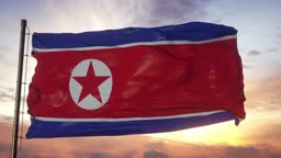 Flag of North Korea waving in the wind against deep beautiful sky at sunset
