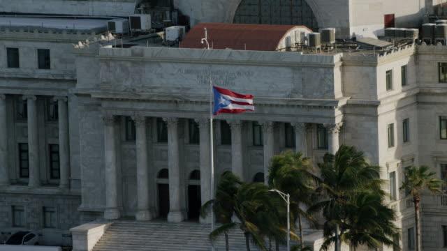 WS AERIAL POV Flag of Puerto Rico waving outside capitol building of Puerto Rico / Old San Juan, San Juan, Puerto Rico, United States