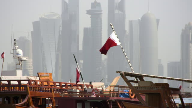 flag of qatar waves in wind above wooden dhow boats and before a massive cityscape of skyscrapers in sunshine - doha, qatar - doha stock videos & royalty-free footage