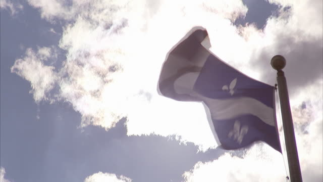flag of quebec the fleurdelise flying on top of pole strong winds partially cloudy sky semibright sun bg fleurdelis emblem white cross blue - quebec flag stock videos & royalty-free footage