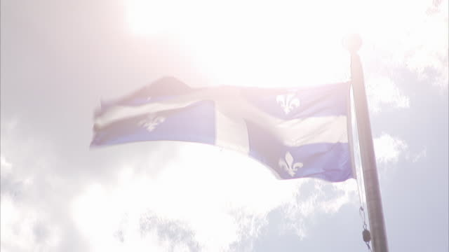 flag of quebec the fleurdelise flying on top of pole strong winds partially cloudy sky bright sun bg fleurdelis emblem white cross blue - quebec flag stock videos & royalty-free footage