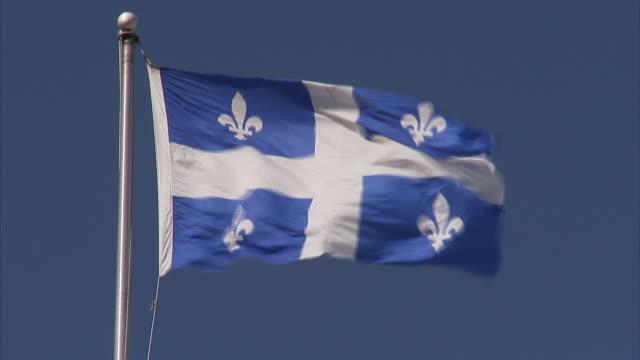 flag of quebec the fleurdelise flying on top of pole strong winds clear sky bg fleurdelis emblem white cross blue - quebec flag stock videos & royalty-free footage