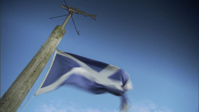 flag of scotland flying on wire attached to wooden pole, flying in strong wind. - scottish flag stock videos & royalty-free footage
