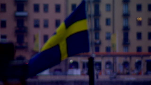 flag of sweden flying on small pole on boat buildings along riddarfjarden bay bg scandinavia quay wharf scandinavian cross blue yellow - swedish flag stock videos and b-roll footage