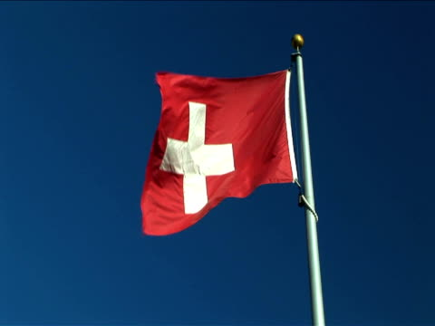 ms, flag of switzerland flapping against clear sky - national flag stock videos & royalty-free footage