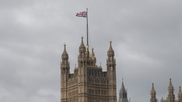 flag of the united kingdom on houses of parliament - bandiera del regno unito video stock e b–roll