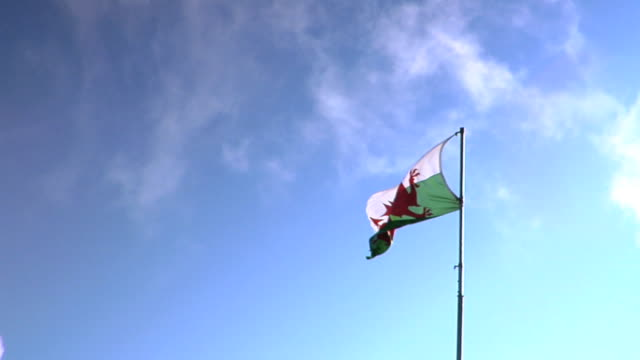 Flag of Wales The Red Dragon flapping in wind on pole some clouds passing by in blue sky BG Red dragon passant green white Welsh Dragon