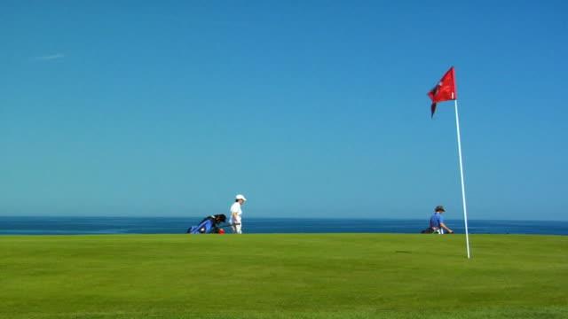 vídeos de stock, filmes e b-roll de ws, flag on golf course, two people passing in background, north truro, massachusetts, usa - bolsa de golfe