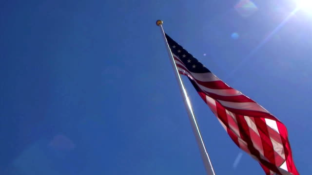 usa flag on pole in sunlight - saluting stock videos & royalty-free footage