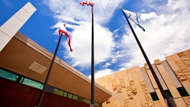 la t/l flag poles with usa and california flags flapping in the wind against blue sky and modern public library building /rancho mirage, california, usa - rancho mirage stock videos & royalty-free footage