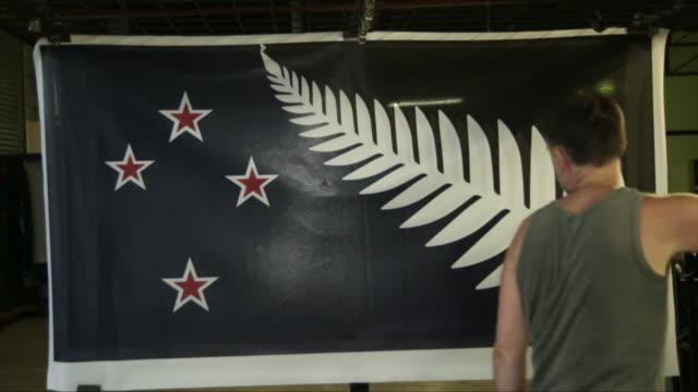 Flag printers print and hang the contending New Zealand flag prior to the New Zealand flag referendum