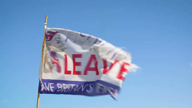 a flag stating 'fishing for leave' blows in wind - brexit stock videos & royalty-free footage