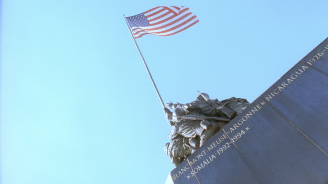 a us flag tops the united states marine corps war memorial in washington, dc. - monumento ai caduti monumento commemorativo video stock e b–roll