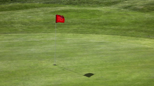 WS Flag waves at 18th hole on golf course / Palma de Mallorca, Mallorca, Baleares, Spain